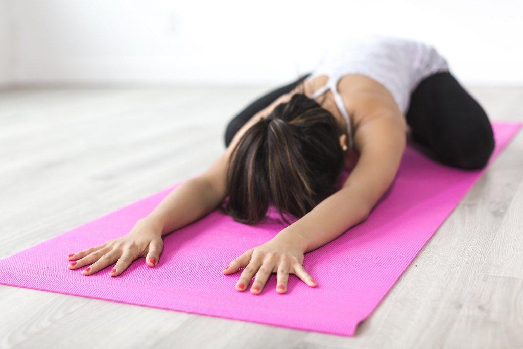 Kvinde laver yogaøvelse på yogamåtte